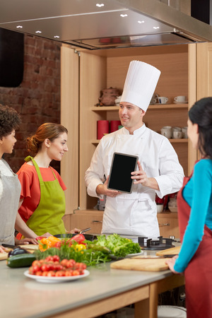 hombre cocinando: clase de cocina, culinario, comida, tecnología y concepto de la gente - mujeres felices con cocinero que muestra la pantalla de Tablet PC en blanco en la cocina