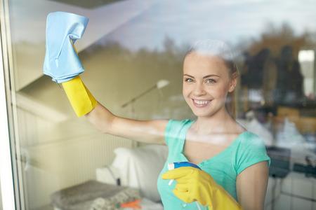 limpieza: las personas, el trabajo doméstico y el concepto de servicio de limpieza - mujer feliz en guantes ventana de limpieza con trapo y spray de limpiador en casa Foto de archivo