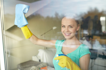 people, housework and housekeeping concept - happy woman in gloves cleaning window with rag and cleanser spray at home Stockfoto