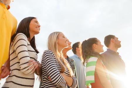 zomervakantie, vakantie en mensen concept - groep gelukkige vrienden kijken op het strand