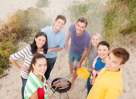 familia pic nic: comida, comer, cocinar, las vacaciones de verano y la gente concepto - grupo de amigos que tienen comida campestre y hacer barbacoa en la playa Foto de archivo