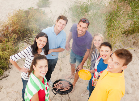 family and friends: food, eating, cooking, summer holidays and people concept - group of friends having picnic and making barbecue on beach
