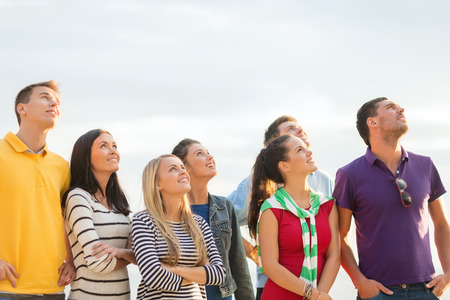 people looking up: summer holidays, vacation and people concept - group of happy friends looking up on beach