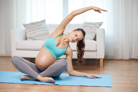 pregnancy yoga: pregnancy, sport, yoga, people and healthy lifestyle concept - happy pregnant woman exercising and stretching on mat at home