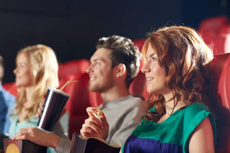 movie theater: cinema, entertainment and people concept - happy friends watching movie in theater