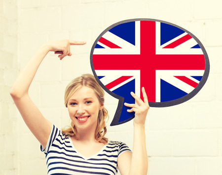 foreign national: education, foreign language, english, people and communication concept - smiling woman holding text bubble of british flag and pointing finger