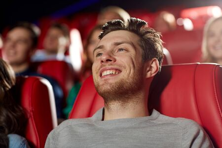 comedy show: cinema, entertainment and people concept - happy young man watching comedy movie in theater