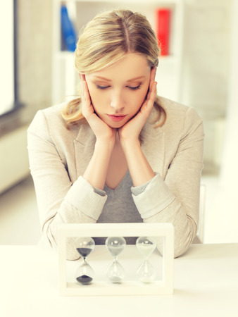 disappoint: picture of pensive businesswoman with sand glass