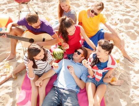Sommerferien, Urlaub, Musik, glückliche Menschen Konzept - Gruppe von Freunden glücklich mit Picknick und Gitarre am Strand