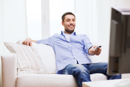 tv remote: home, technology, people and entertainment concept - smiling man with tv remote control at home
