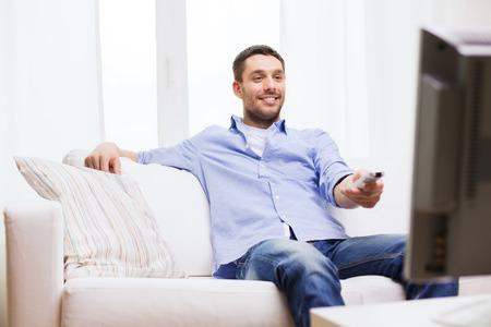 Thuis, technologie, mensen en entertainment concept - lachende man met tv afstandsbediening thuis Stockfoto - 40250556
