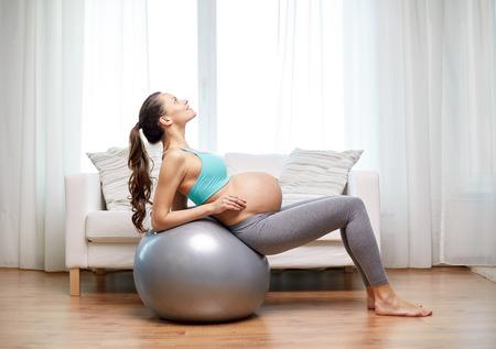 gymnastique: la grossesse, sport, fitness, les gens et le concept de mode de vie sain - femme enceinte heureux exerçant sur fitball à la maison