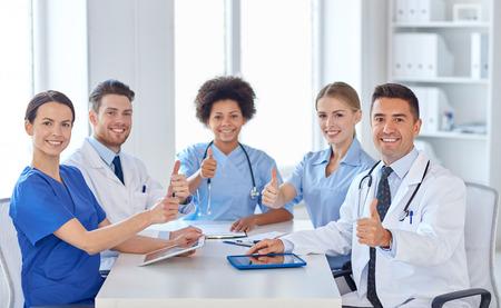 ziekenhuis, beroep, mensen en geneeskunde concept - groep gelukkige artsen vergadering op medische kantoor
