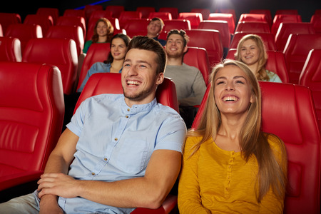 auditorium: cinema, entertainment and people concept - happy friends watching comedy movie in theater
