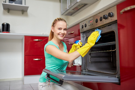 people, housework and housekeeping concept - happy woman with bottle of spray cleanser cleaning oven at home kitchen Foto de archivo