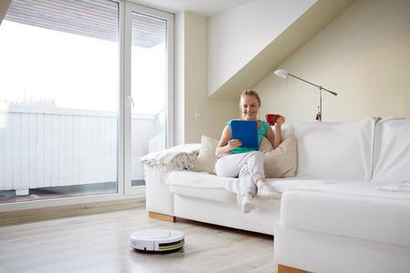 사람, 가사 및 기술 개념 - 집에서 차를 마시는 태블릿 PC 컴퓨터와 로봇 진공 청소기와 함께 행복 한 여자