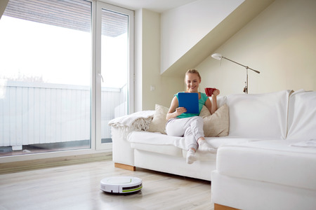 people, housework and technology concept - happy woman with tablet pc computer and robot vacuum cleaner drinking tea at home Stockfoto