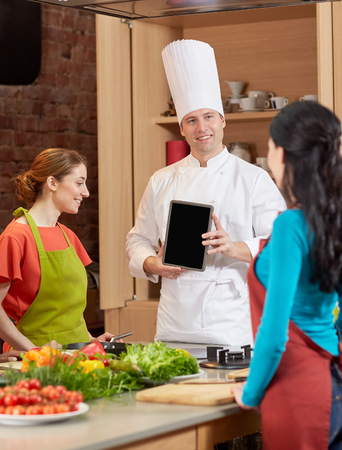food technology: cooking class, culinary, food, technology and people concept - happy women with chef cook showing blank tablet pc screen in kitchen