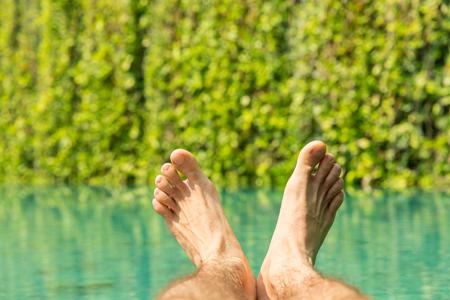 pies masculinos: el ocio, la gente, los viajes y el turismo concepto - cerca de pies masculinos más complejo de la piscina