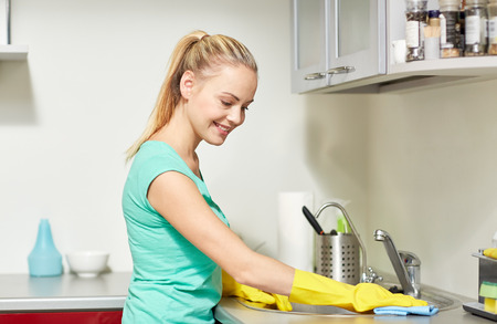 protective gloves: people, housework and housekeeping concept - happy woman in protective gloves cleaning table with rag at home kitchen