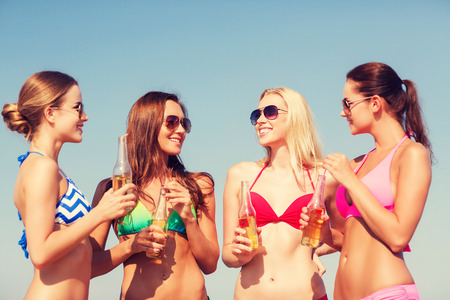 nonalcoholic beer: summer vacation, holidays, travel and people concept - group of smiling young women sunbathing and drinking on beach