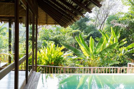 bungalow: leisure, travel and tourism concept - swimming pool and bungalow at hotel resort