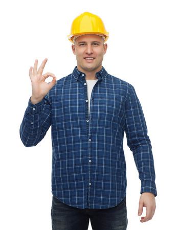 ok: repair, construction, building, people and maintenance concept - smiling male builder or manual worker in helmet showing ok sign Stock Photo