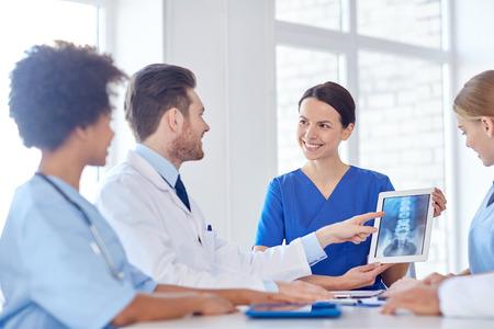 ziekenhuis, beroep, mensen en geneeskunde concept - groep gelukkige artsen met een tablet pc computers vergadering op medische kantoor Stockfoto