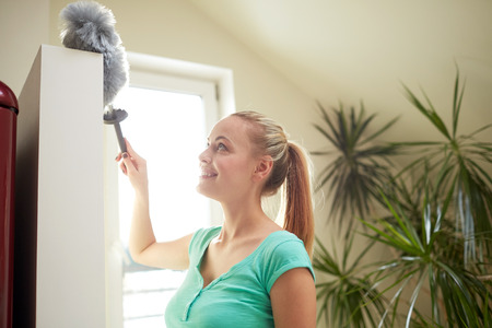 people, housework and housekeeping concept - happy woman with duster cleaning at home Stock Photo