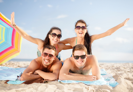 gente feliz: vacaciones de verano, vacaciones y la gente concepto - grupo de amigos felices divertirse y tomar el sol en la playa