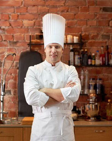 ready to cook food: cooking and people concept - happy male chef cook with crossed hands in restaurant kitchen Stock Photo