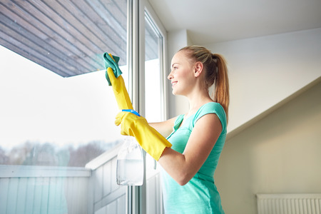 people, housework and housekeeping concept - happy woman in gloves cleaning window with rag and cleanser spray at home Standard-Bild