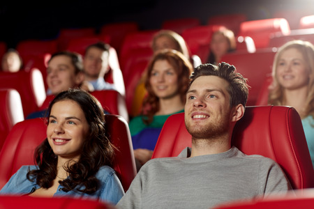 movie: cinema, entertainment and people concept - happy friends watching movie in theater