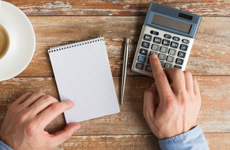 business, education, people and technology concept - close up of male hands with calculator, pen and notebook on table