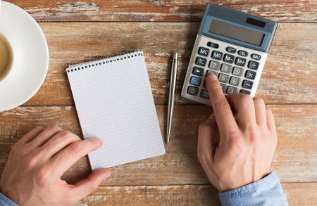 calculadora: negocio, la educación, las personas y la tecnología concepto - Cerca de las manos masculinas con calculadora, lápiz y cuaderno en la mesa