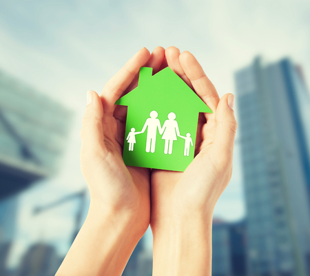 energy symbol: real estate and family home concept - closeup picture of female hands holding green paper house with family Stock Photo