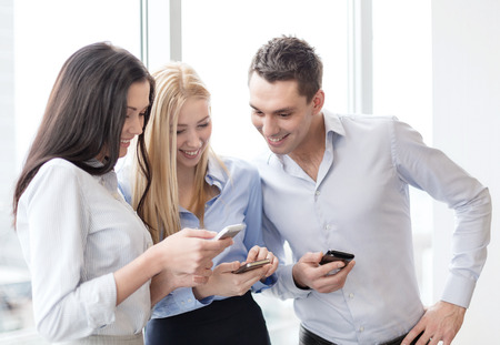 person looking: business and technology concept - smiling business team with smartphones in office Stock Photo