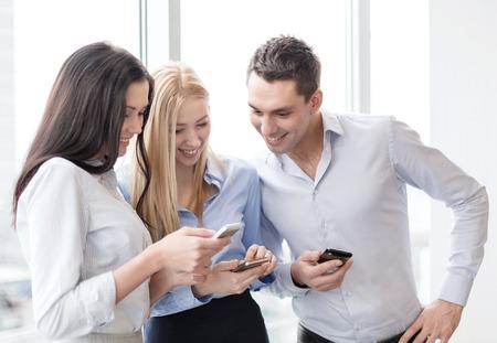 Business und Technologie-Konzept - lächelnd Business-Team mit Smartphones im Amt