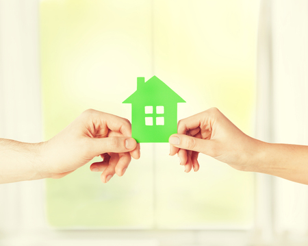 dream home: closeup picture of woman and man hands holding green house