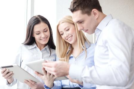 ビジネスやオフィスのコンセプト - ビジネス チーム オフィスでタブレット pc での作業を笑顔