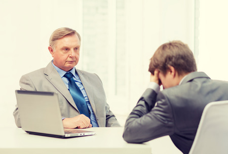 angry businessman: business, technology and office concept - older man and young man having argument in office Stock Photo