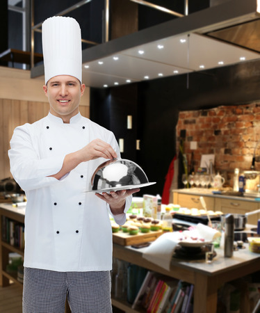 cloche: cooking, profession and people concept - happy male chef cook holding cloche over restaurant kitchen Stock Photo