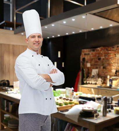 料理、職業、人のコンセプト - 幸せな男性シェフ調理の交差させた手レストランのキッチンで