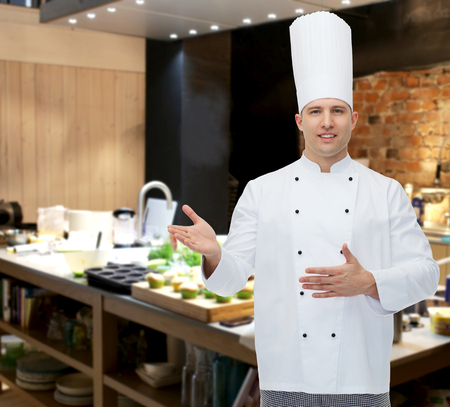 inviting: cooking, profession and people concept - happy male chef cook inviting