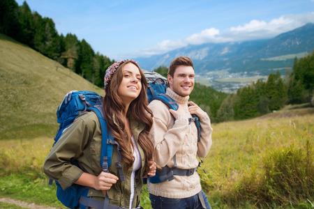 avontuur, reizen, toerisme, wandelen en mensen concept - lachend paar wandelen met rugzakken over alpine heuvels achtergrond Stockfoto