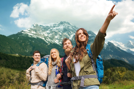 adventure, travel, tourism, hike and people concept - group of smiling friends with backpacks pointing finger over alpine mountains background