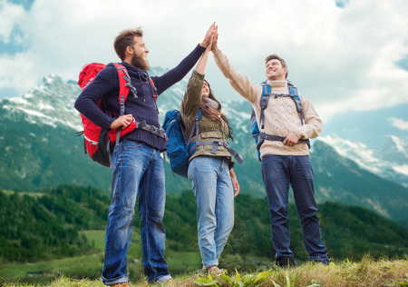 hike: travel, tourism, hike, gesture and people concept - group of smiling friends with backpacks making high five over alpine mountains background