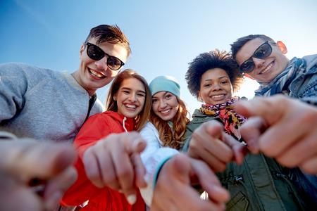 mensen, vrije tijd, gebaar en tienerconcept - groep gelukkige tienervrienden die vingers op stadsstraat richten
