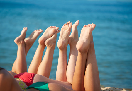 lying on back: summer vacation, holidays, travel and people concept - close up of young women lying on beach from back