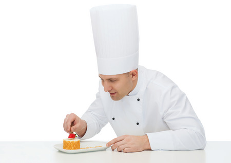 pastries: cooking, profession, haute cuisine, food and people concept - happy male chef cook decorating dessert Stock Photo